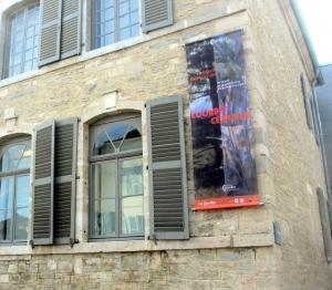 L'affiche de l'exposition fixé sur le musée Courbet à Ornans
